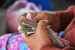 A person counts a stack of paper currency.