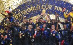 A group of men celebrate with the World Cup trophy amidst a shower of confetti