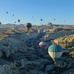 Hot air balloons hover over a scenic valley in Cappadocia, Turkey