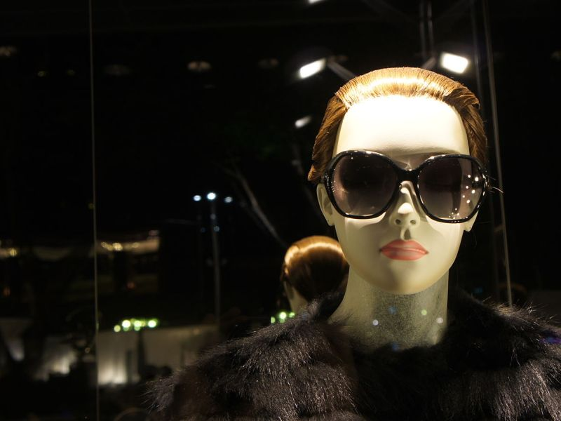 Female mannequin with black fur and sunglasses.