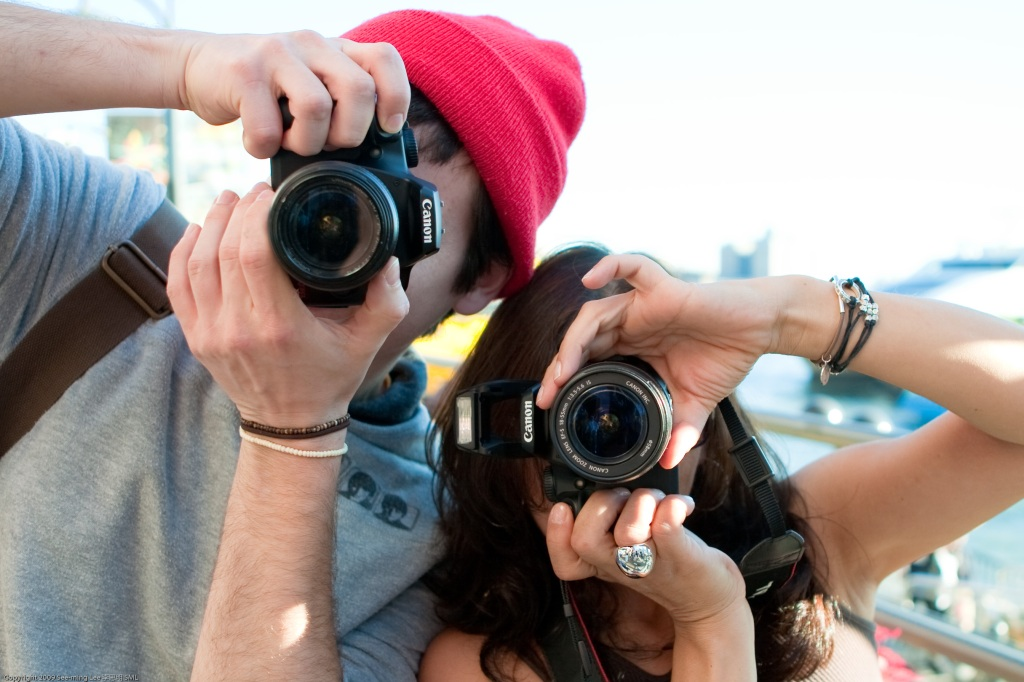 Photograph of two people holding cameras and apearing to photograph the viewer