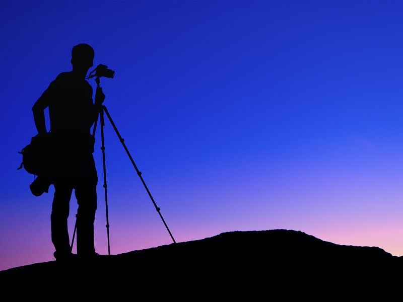 Silhouette of a photographer and tripod standing on top of a hill. It is sunset or sunrise and the sky is clear with a bold colour gradient from blue to violet to yellow.